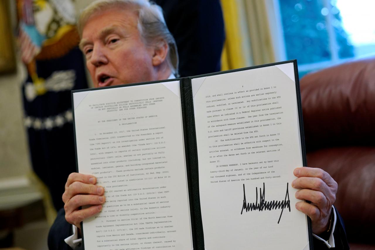 Trump signs directives to impose tariffs on washing machines and solar panels in the Oval Office at the White House in Washington
